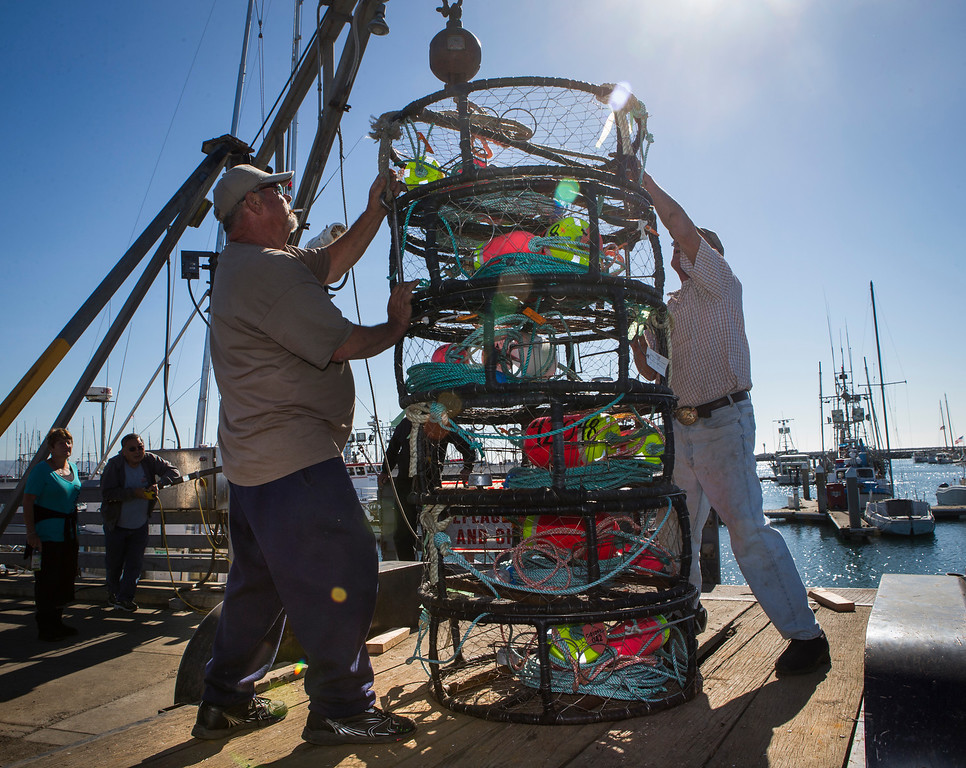 ". Fishermen Bill Webb, left and Dutch Freeman, right , load crab pots onto the ""Cricket\"". (John Green/Bay Area News Group)"