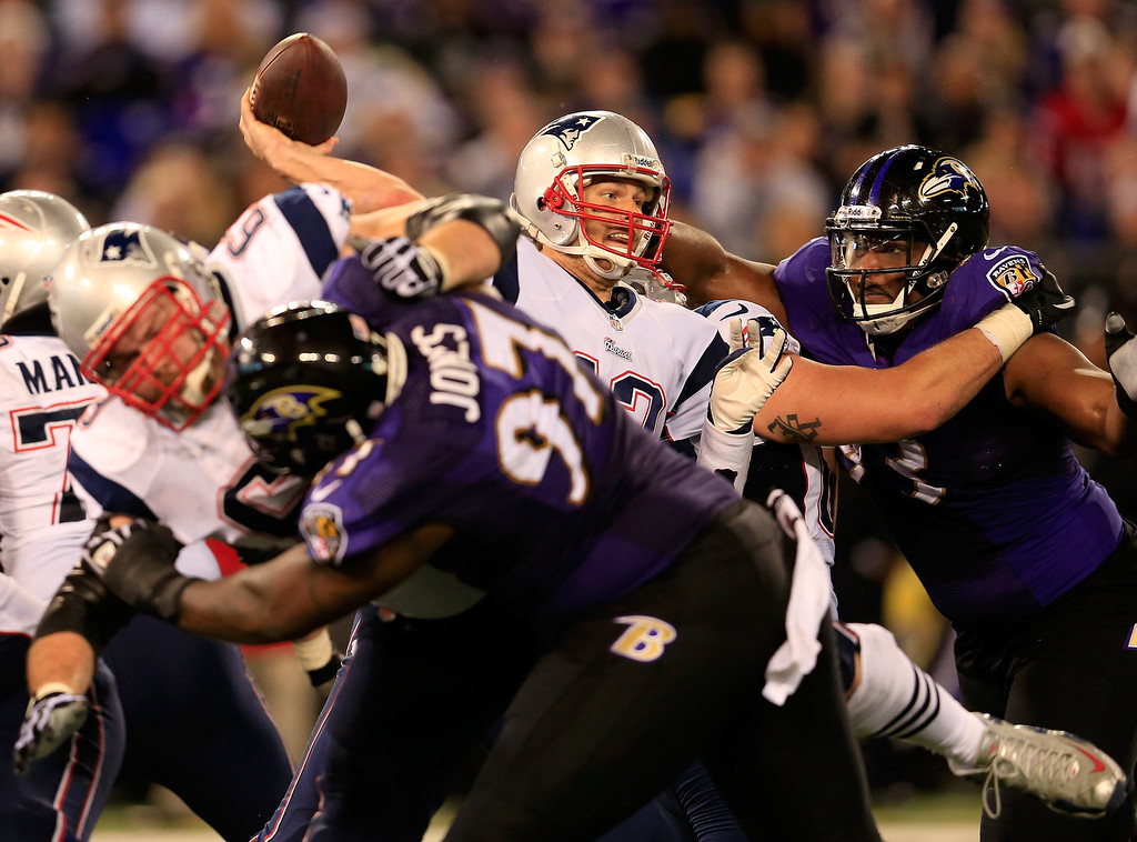. Quarterback Tom Brady #12 of the New England Patriots gets off a second half pass while being pressured by defensive end DeAngelo Tyson #93 of the Baltimore Ravens during the Patriots 41-7 win at M&T Bank Stadium on December 22, 2013 in Baltimore, Maryland.  (Photo by Rob Carr/Getty Images)