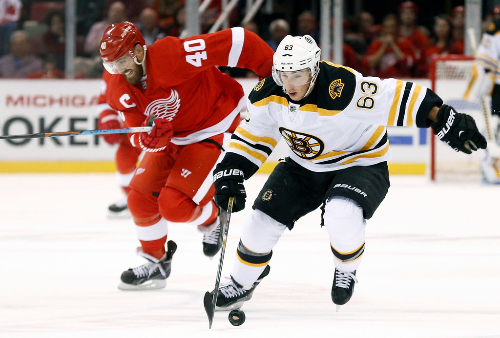 . Boston Bruins left wing Brad Marchand (63) breaks away from Detroit Red Wings\' Henrik Zetterberg, of Sweden, in the first period of a NHL hockey game in Detroit Thursday, Oct. 9, 2014. (AP Photo/Paul Sancya)