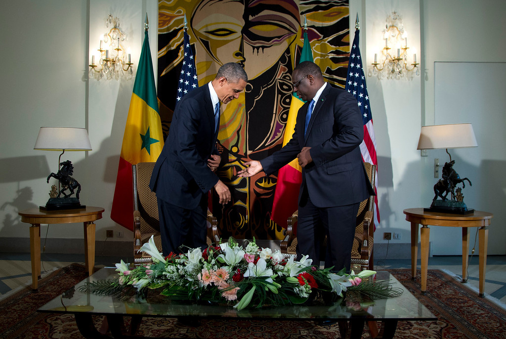 . Senegalese President Macky Sall, right, gestures for U.S. President Barack Obama to sit during a bilateral meeting at the Presidential Palace on Thursday, June 27, 2013, in Dakar, Senegal. President Obama landed in Senegal Wednesday night to kick off a weeklong trip to Africa, a three-country visit aimed at overcoming disappointment on the continent over the first black U.S. president\'s lack of personal engagement during his first term. (AP Photo/Evan Vucci)