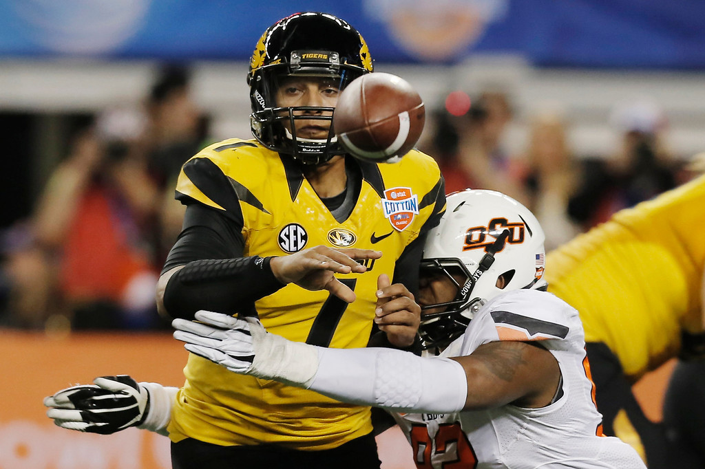 . Missouri quarterback James Franklin (1) throws the ball to running back Henry Josey as Oklahoma State defensive end Jimmy Bean (92) defends during the first half of the Cotton Bowl NCAA college football game on Friday, Jan. 3, 2014, in Arlington, Texas. (AP Photo/Brandon Wade)