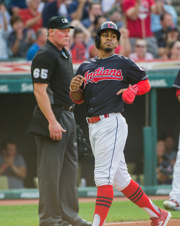 . Cleveland Indians\' Francisco Lindor scores on a single by Carlos Santana off Kansas City Royals starting pitcher Jason Hammel as umpire Ted Barrett watches the play, during the third inning of a baseball game in Cleveland, Saturday, Sept. 16, 2017. (AP Photo/Phil Long)