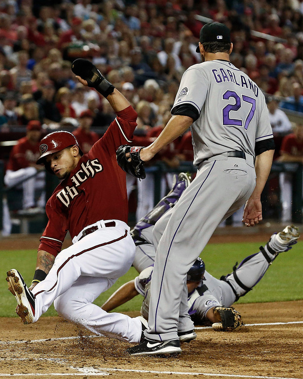 . Arizona Diamondbacks\' Gerardo Parra, left, avoids the tag of Colorado Rockies\' Wilin Rosario, bottom right, and Rockies pitcher Jon Garland (27) to score a run during the third inning of a baseball game on Sunday, April 28, 2013, in Phoenix. (AP Photo/Ross D. Franklin)