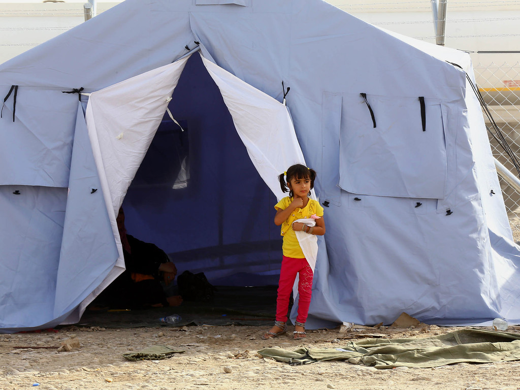 . An Iraqi refugee girl from Mosul stands outside her family\'s tent at Khazir refugee camp outside Irbil, 217 miles (350 kilometers) north of Baghdad, Iraq, Wednesday, June. 11, 2014. The Islamic State of Iraq and the Levant, the al-Qaida breakaway group, on Monday and Tuesday took over much of Mosul in Iraq and then swept into the city of Tikrit further south. An estimated half a million residents fled Mosul, the economically important city. (AP Photo)
