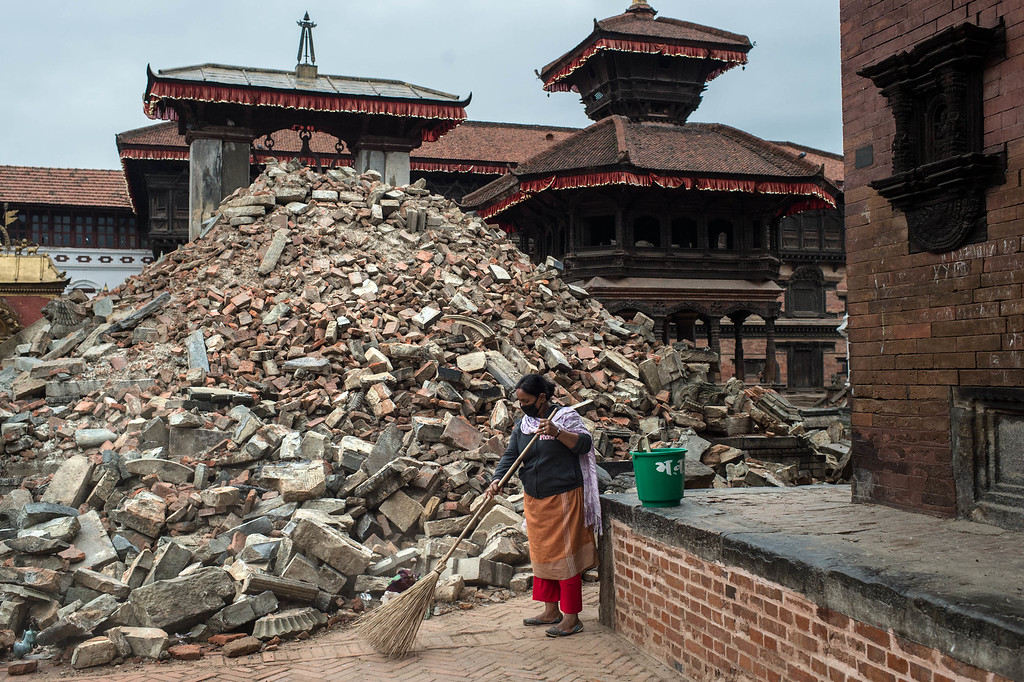 . A woman sweeps the street next to debris of a collapsed temple at Durbar square in Bhaktapur on April 30, 2015 in Kathmandu, Nepal. A major 7.8 earthquake hit Kathmandu mid-day on Saturday, and was followed by multiple aftershocks that triggered avalanches on Mt. Everest that buried mountain climbers in their base camps. Many houses, buildings and temples in the capital were destroyed during the earthquake, leaving over 5500 dead and many more trapped under the debris as emergency rescue workers attempt to clear debris and find survivors. Regular aftershocks have hampered recovery missions as locals, officials and aid workers attempt to recover bodies from the rubble.  (Photo by David Ramos/Getty Images)