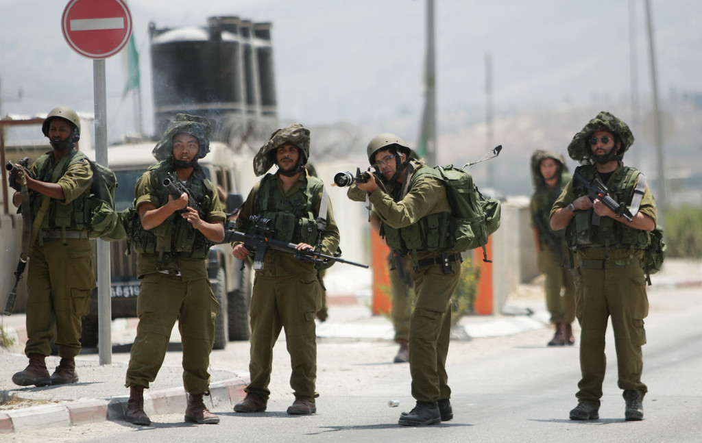 . Israeli soldiers shoot tear gas towards Palestinian protesters during a demonstration against the Israeli military action in Gaza, at Hawara checkpoint near the West Bank city of Nablus, Tuesday, July 22, 2014. (AP Photo/Nasser Ishtayeh)