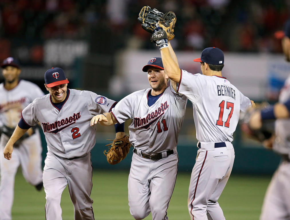 . Minnesota Twins\' Clete Thomas, center, is congratulated by Doug Bernier, right, and Brian Dozier after catching the ball over the fence in the eighth inning Monday, July 22, 2013, in Anaheim, Calif. (AP Photo/Jae C. Hong)
