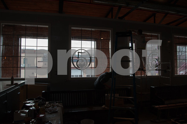 02/02/18 Wesley Bunnell | Staff Steve Simeone of New Cambridge Painting puts finishing touches on inside windows at Five Churches Brewery located at 193 Arch St. as the brewery's logo is visible in a second floor window.