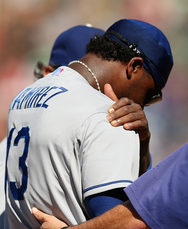 . CHICAGO, IL - AUGUST 04:  Hanley Ramirez #13 of the Los Angeles Dodgers grabs his shoulder as he leaves the field after hitting the wall along the third base line catching a fly ball hit by David DeJesus of the Chicago Cubs in the 7th inning at Wrigley Field on August 4, 2013 in Chicago, Illinois. The Dodgers defeated the Cubs 1-0.  (Photo by Jonathan Daniel/Getty Images)