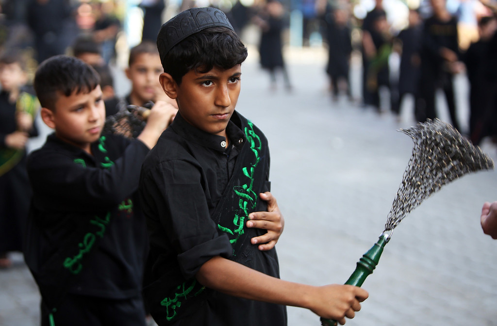 . Iraqi Shiite men beat themselves with chains as part of a self-flagellation ritual during a parade in preparation for the peak of the mourning period of Ashura in Baghdad\'s northern district of Kadhimiya on November 1, 2014.  AHMAD AL-RUBAYE/AFP/Getty Images