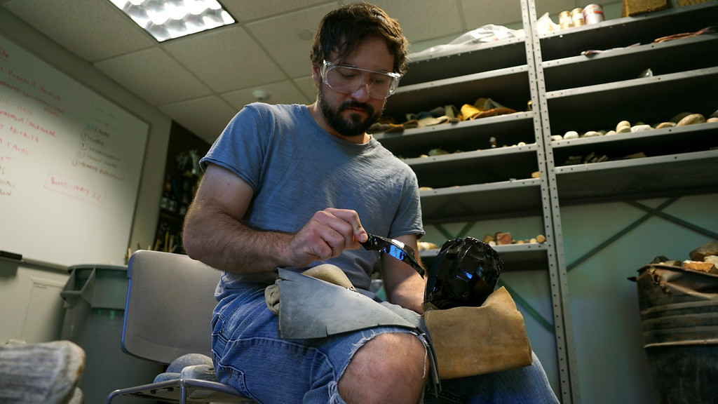 . In this June 1, 2017, photo, Metin Eren, an archaeologist at Kent State University, peers at a newly chipped flake of obsidian in Kent, Ohio. Eren runs a newly-opened laboratory which makes replicas of ancient arrows, knives, and pottery to be shot, crushed, and smashed. It\'s allowing researchers to learn about engineering techniques of the first native Americans without destroying priceless genuine relics in the process. (AP Photo/Dake Kang)