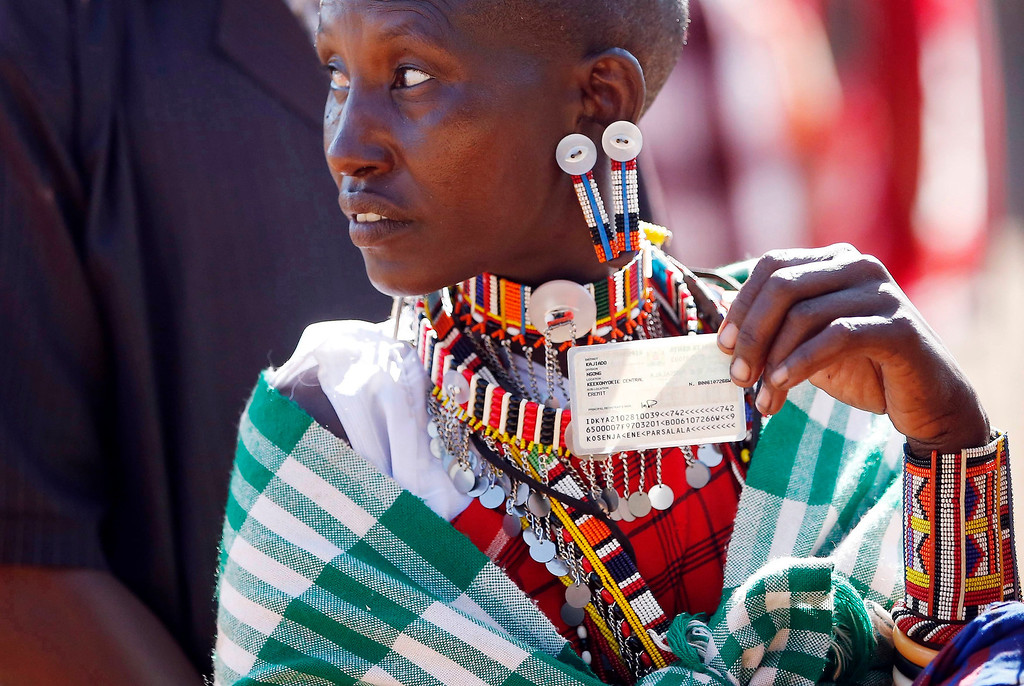 . A Masai woman holds her ID card as she waits to cast her ballot in a polling station during the presidential and parliamentary elections near town of Magadi some 85 km (53 miles) south of Nairobi. REUTERS/Goran Tomasevic