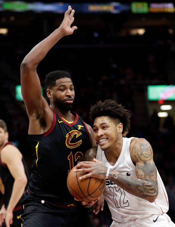 . Washington Wizards\' Kelly Oubre Jr. (12) drives past Cleveland Cavaliers\' Tristan Thompson (13) in the second half of an NBA basketball game, Thursday, April 5, 2018, in Cleveland. (AP Photo/Tony Dejak)