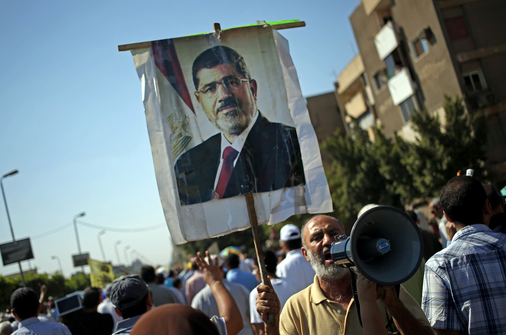 . Supporters of Egypt\'s ousted President Mohammed Morsi, seen on a poster, chant slogans against Egyptian Defense Minister Gen. Abdel-Fattah el-Sissi, during a protest in Cairo, Egypt, Friday, Oct. 11, 2013. Supporters of ousted president Mohammed Morsi are holding scattered protests across Egypt, calling off a planned rally at Cairo\'s iconic Tahrir Square almost a week after bloody clashes left nearly 60 dead. (AP Photo/Khalil Hamra)