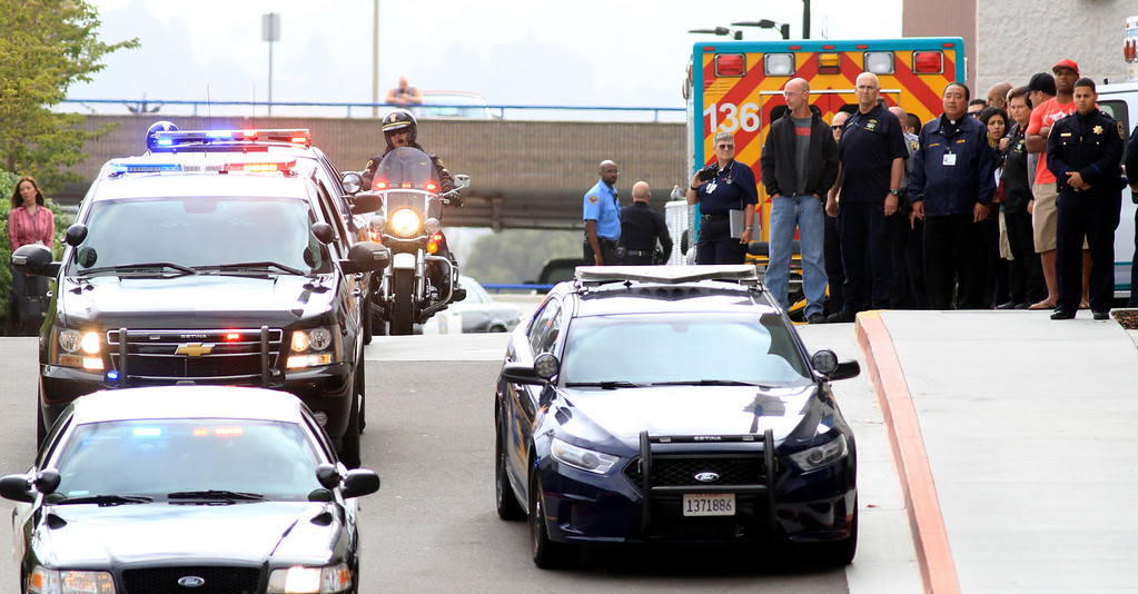 . Fellow law enforcement members watch as Hayward police escort the Alameda County Coroner\'s van carrying Sergeant Scott Lunger from Eden Medical Center in Castro Valley, Calif., on Wednesday, July 22, 2015.  Lunger was shot and killed in a shooting during a traffic stop early Wednesday morning. (Laura A. Oda/Bay Area News Group)