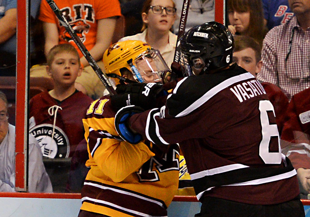 . Union College junior defenseman Charlie Vasaturo, right, slams Minnesota junior forward Sam Warning into the glass in the second period of the NCAA Frozen Four Championship Game at the Wells Fargo Center in Philadelphia, Saturday, April 12, 2014.  (Pioneer Press: John Autey)