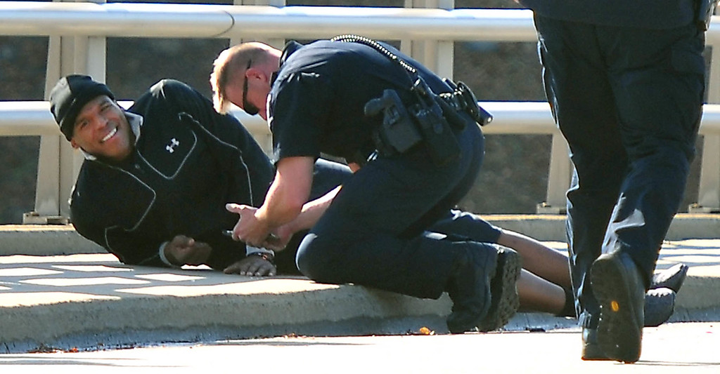 . A Charlotte-Mecklenburg police officer tends to Carolina Panthers NFL football quarterback Cam Newton following a two-vehicle crash not far from the team\'s stadium in Charlotte, N.C., Tuesday, Dec. 9, 2014. (AP Photo/The Charlotte Observer, Todd Sumlin)