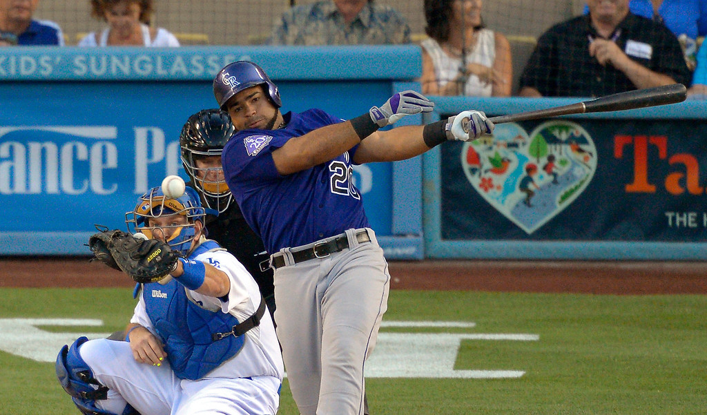. Colorado Rockies\' Wilin Rosario, right, hits an RBI single as Los Angeles Dodgers catcher A.J. Ellis catches during the first inning of their baseball game, Friday, July 12, 2013, in Los Angeles.  (AP Photo/Mark J. Terrill)