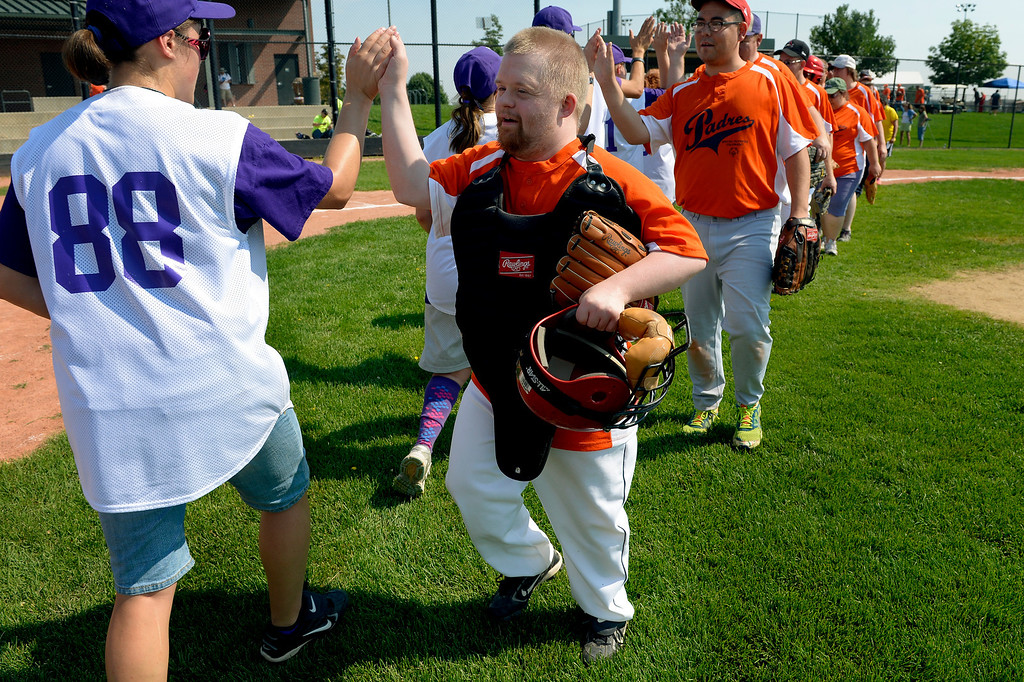 . DENVER, CO. - AUGUST 17: Catcher Ryan Haug, of the Colorado Springs Padres, leads his team following their victory over the Parker Power during in the first round of the Special Olympics softball state championship at the Lowry Sports Complex in Denver, CO August 17, 2013. Special Olympics Colorado hosted its state championship in Bocce, Cycling, Golf, Softball and Tennis. Six hundred athletes competed in the events, which was supported by 250 volunteers and coaches. (Photo By Craig F. Walker / The Denver Post)