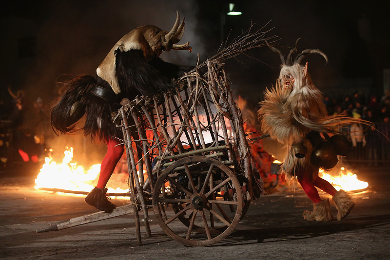 . A member of the Haiminger Krampusgruppe dressed as the Krampus creature attacks a cart where a delinquent little boy is captive on the town square during their annual Krampus night in Tyrol on December 1, 2013 in Haiming, Austria. Krampus, in Tyrol also called Tuifl, is a demon-like creature represented by a fearsome, hand-carved wooden mask with animal horns, a suit made from sheep or goat skin and large cow bells attached to the waist that the wearer rings by running or shaking his hips up and down. Krampus has been a part of Central European, alpine folklore going back at least a millennium, and since the 17th-century Krampus traditionally accompanies St. Nicholas and angels on the evening of December 5 to visit households to reward children that have been good while reprimanding those who have not. However, in the last few decades Tyrol in particular has seen the founding of numerous village Krampus associations with up to 100 members each and who parade without St. Nicholas at Krampus events throughout November and early December.  (Photo by Sean Gallup/Getty Images)