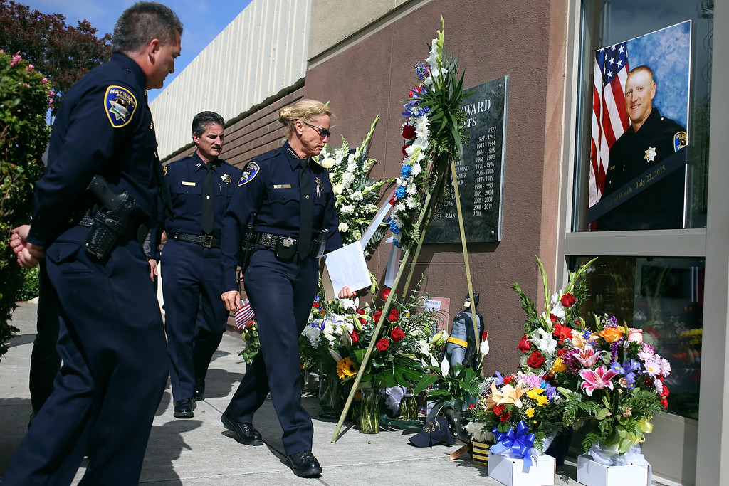 . Hayward Police Lt. Eric Krimm, Capt. Jason Martinez and Police Chief  Diane Urban, from left, walk past a memorial for Sgt. Scott Lunger following a news conference outside the police station in Hayward, Calif., Wednesday, July 22, 2015. Urban confirmed the arrest of one suspect, Mark Anthony Estrada, 21, of Oakland, in connection with the fatal shooting of Sgt. Scott Lunger during a traffic stop early Wednesday morning near Lion and Myrtle Streets. (Anda Chu/Bay Area News Group)