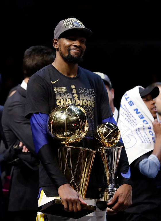 . Golden State Warriors\' Kevin Durant holds the NBA championship and MVP trophies after the Warriors defeated the Cleveland Cavaliers 108-85 in Game 4 of basketball\'s NBA Finals to win the NBA championship, Friday, June 8, 2018, in Cleveland. (AP Photo/Tony Dejak)