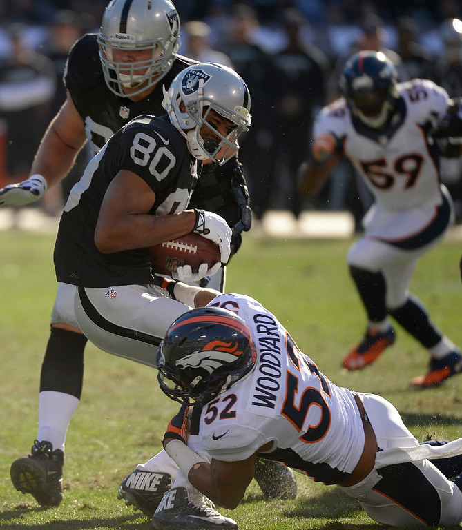 . Denver Broncos middle linebacker Wesley Woodyard (52) puts a hit on Oakland Raiders wide receiver Rod Streater (80) for a loss of yards during the first quarter at O.co Coliseum. (Photo by John Leyba/The Denver Post)
