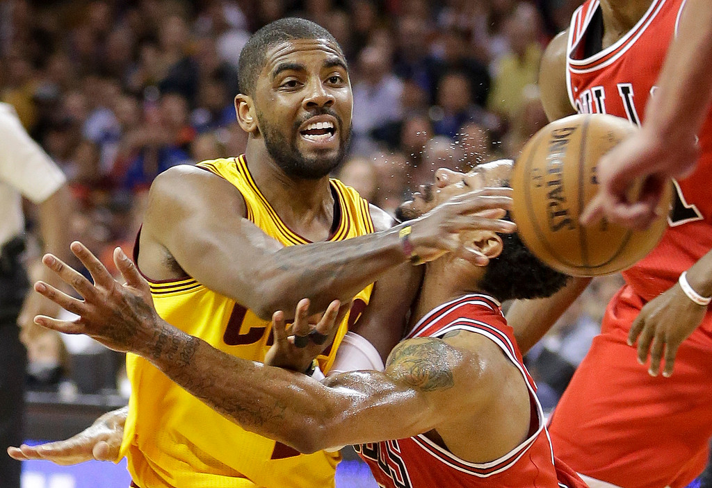 . Cleveland Cavaliers guard Kyrie Irving (2) passes off the as Chicago Bulls guard Derrick Rose defends during the second half of Game 5 in a second-round NBA basketball playoff series Tuesday, May 12, 2015, in Cleveland. (AP Photo/Tony Dejak)