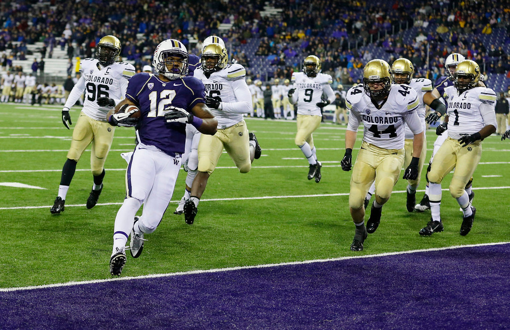. Washington running back Dwayne Washington (12) runs for a touchdown against Colorado in the second half of an NCAA college football game on Saturday, Nov. 9, 2013, in Seattle. Washington won 59-7. (AP Photo/Ted S. Warren)
