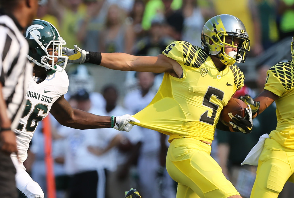 . Michigan State\'s R. J. Williamson, left, tries to hang on to Oregon\'s Devon Allen after a reception, but Allen broke free for a touchdown during the 2nd quarter of their NCAA college football game in Eugene, Oregon, Saturday Sept. 6, 2014. (AP Photo/Chris Pietsch)