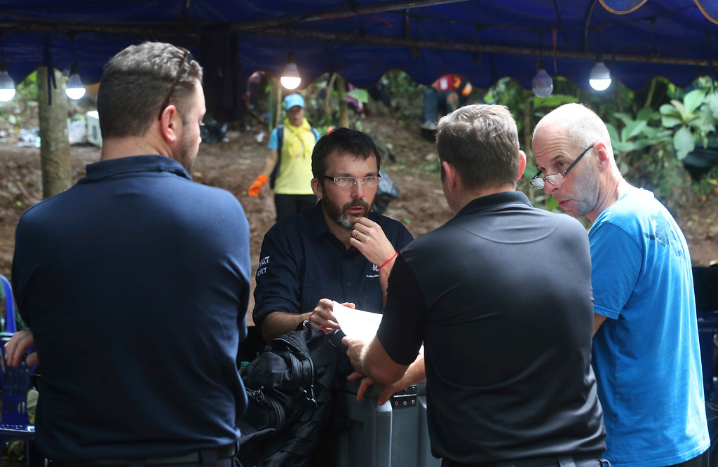 . In this Thursday, July 2018, file photo, Australian Federal Police and Defense Force personnel talk about extraction plans to get 12 boys and their soccer coach out of a flooded cave in Mae Sai, Chiang Rai province, in northern Thailand. (AP Photo/Sakchai Lalit, File)