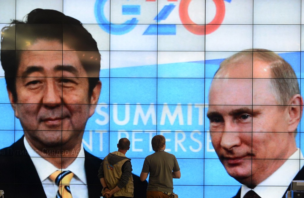 . Journalists walk past a screen in the media center showing Russias President Vladimir Putin and Japans Prime Minister Shinzo Abe during the G20 summit on September 5, 2013 in Saint Petersburg.  AFP PHOTO / KIRILL KUDRYAVTSEV/AFP/Getty Images