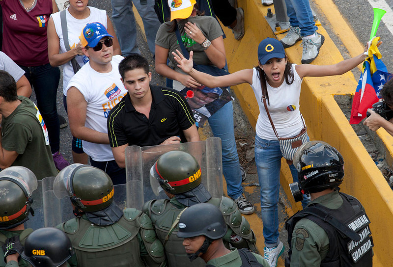 . Opposition supporters and students confront riot police as they block on a highway in the Altamira neighborhood of Caracas, Venezuela, Monday, April 15, 2013. National Guard troops dispersed students protesting the official results of Venezuela\'s disputed presidential election. Opposition candidate Henrique Capriles has challenged his narrow loss to Nicolas Maduro and is demanding a recount. (AP Photo/Ramon Espinosa)