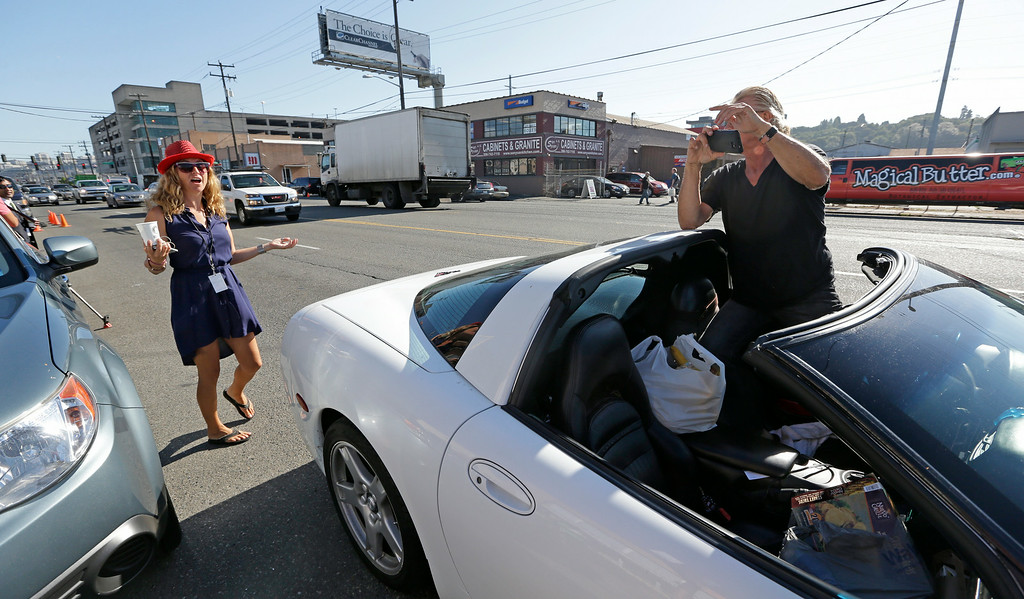 . Melissa McKelvey, left, urges driver Terry Martin, blocking traffic, to move along from in front of Cannabis City, on the first day that sales of recreational pot is legal in the state Tuesday, July 8, 2014, in Seattle. The shop is the first and, initially, only store in Seattle to legally sell pot. (AP Photo/Elaine Thompson)