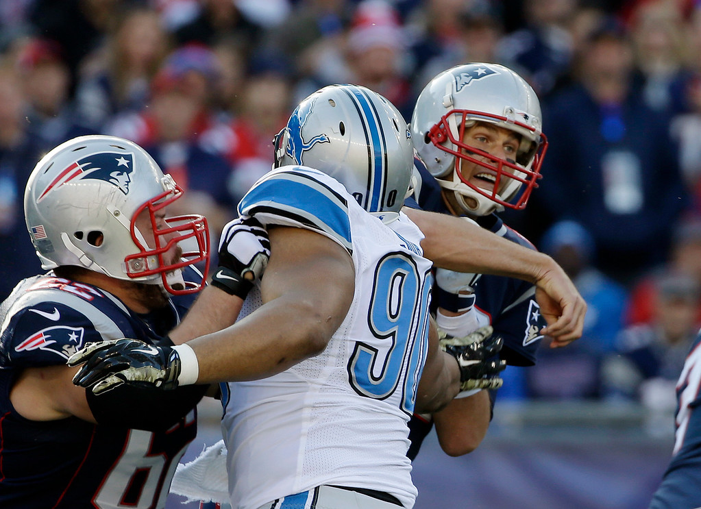 . New England Patriots quarterback Tom Brady, right, follows through on a pass against the rush by Detroit Lions defensive tackle Ndamukong Suh (90) in the first half of an NFL football game Sunday, Nov. 23, 2014, in Foxborough, Mass. (AP Photo/Steven Senne)