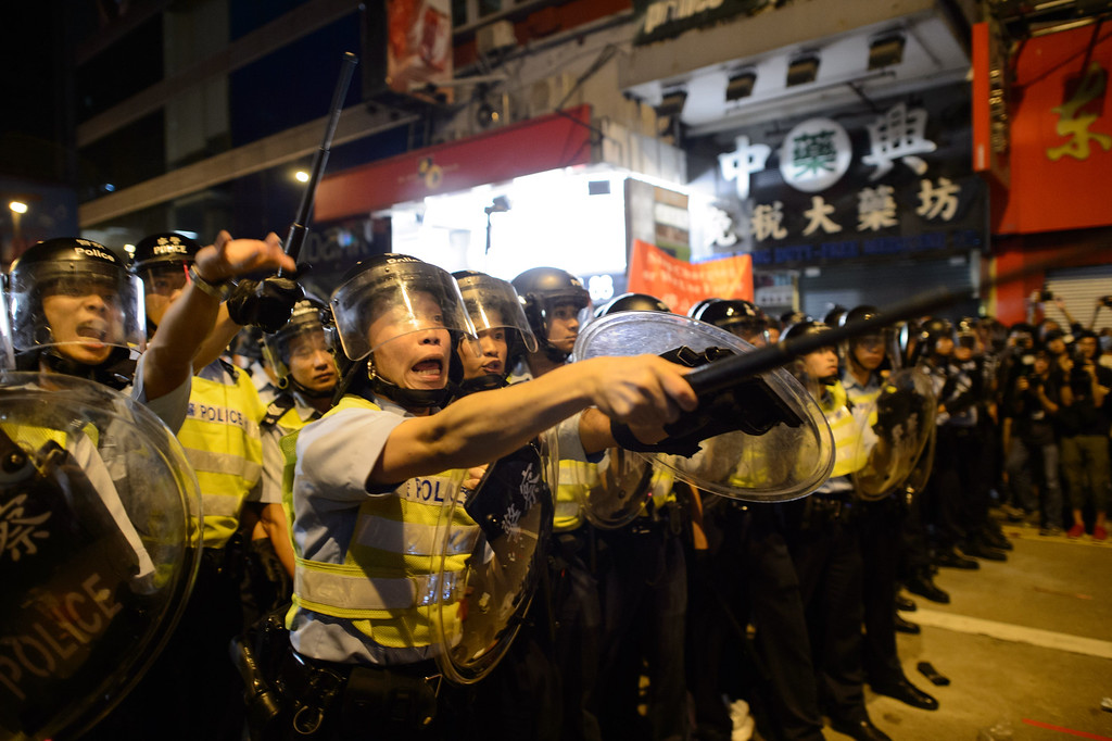 . Policemen holding batons advance towards pro-democracy protesters gestures during clashes on a street in the Mong Kok district of Hong Kong early on October 19, 2014.Hong Kong\'s embattled government said it will open talks with student demonstrators on October 21, after three nights of violent clashes between police and protesters who have paralysed parts of the city with mass pro-democracy rallies.   AFP PHOTO / Ed JonesED JONES/AFP/Getty Images