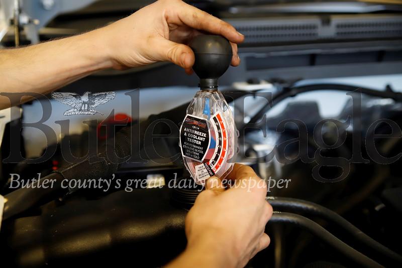 Baglier Buick GMC technician Hunter Romito checks a vehicle's coolant. Seb Foltz/Butler Eagle