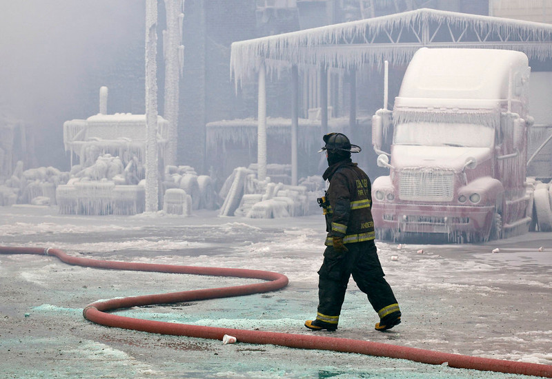 . A firefighter walks past an ice covered warehouse that caught fire on Tuesday night in Chicago January 23, 2013. Fire department officials said it is the biggest fire the department has had to battle in years and one-third of all Chicago firefighters were on the scene at one point or another trying to put out the flames. An Arctic blast continues to gripped the U.S. Midwest and Northeast Wednesday, with at least three deaths linked to the frigid weather, and fierce winds made some locations feel as cold as 50 degrees below zero Fahrenheit. (minus 46 degrees Celsius) REUTERS/John Gress