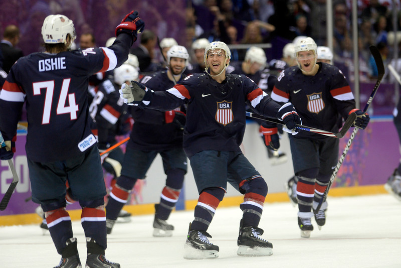 . Teammates skate onto the ice to celebrate with T.J. Oshiet (74) of the U.S.A. after he made a game-winning shot on Sergei Bobrovski (72) of the Russia during  the U.S.A.\'s shootout-win at Bolshoy arena. Sochi 2014 Winter Olympics on Saturday, February 15, 2014. (Photo by AAron Ontiveroz/The Denver Post)