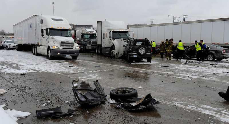 . Authorities search a section of multi-vehicle accident on Interstate 75 is shown in Detroit, Thursday, Jan. 31, 2013. Snow squalls and slippery roads led to a series of accidents that left at least three people dead and 20 injured on a mile-long stretch of southbound I-75. More than two dozen vehicles, including tractor-trailers, were involved in the pileups.  (AP Photo/The Detroit News, David Coates)