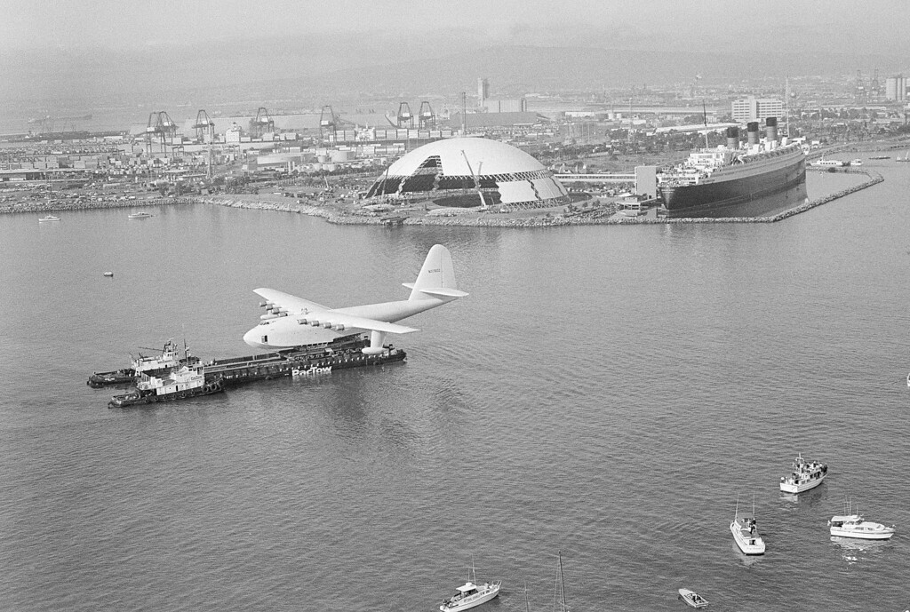 ". ""Spruce Goose,\"" the flying boat belonging to the late millionaire Howard Hughes, is gingerly edged across the Los Angeles harbor near Long Beach, Calif., by two tugs pushing a barge on which the huge plane is mounted, during the move, Feb. 12, 1982.  The plane will be put on public display next to another popular attraction, the former luxury liner Queen Mary, right, background.  (AP Photo/Wally Fong)"