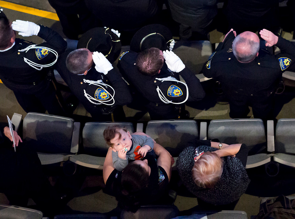 . Police officers salute as a small child is distracted by the media during the Memorial service for Santa Cruz polio detective Loran \'Butch\' Baker and detective Elizabeth Butler on Thursday at the HP Pavilion in San Jose. (Kevin Johnson/Senntnel)