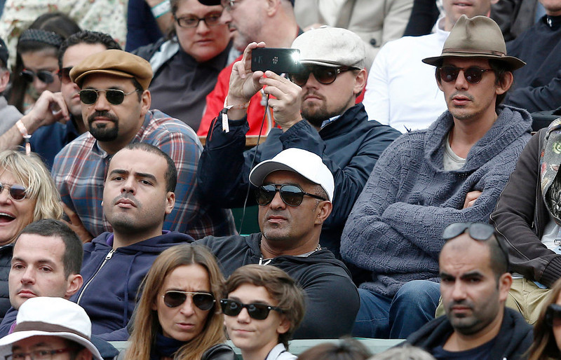 . US actor Leonardo di Caprio (C) takes a picture as he attends a French tennis Open round of 16 match at the Roland Garros stadium in Paris on June 2, 2013.  MARTIN BUREAU/AFP/Getty Images