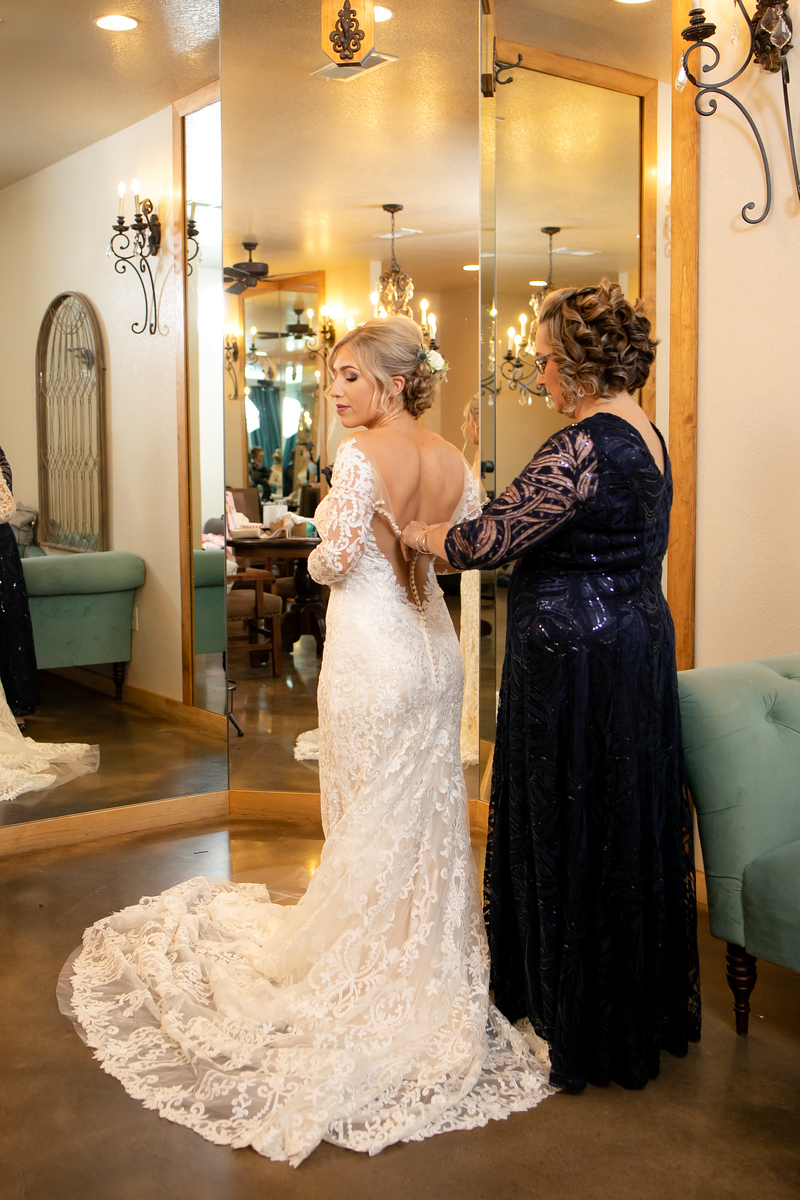 a bride getting her lace wedding dress zipped up by her mother just before her wedding ceremony