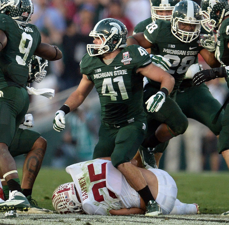 . Michigan State linebacker Kyler Elsworth (41) stands over Stanford running back Tyler Gaffney (25) after a tackle in the second half of the 100th Rose bowl game in Pasadena, Calif., on Wednesday, Jan.1, 2014. Michigan State won 24-20.