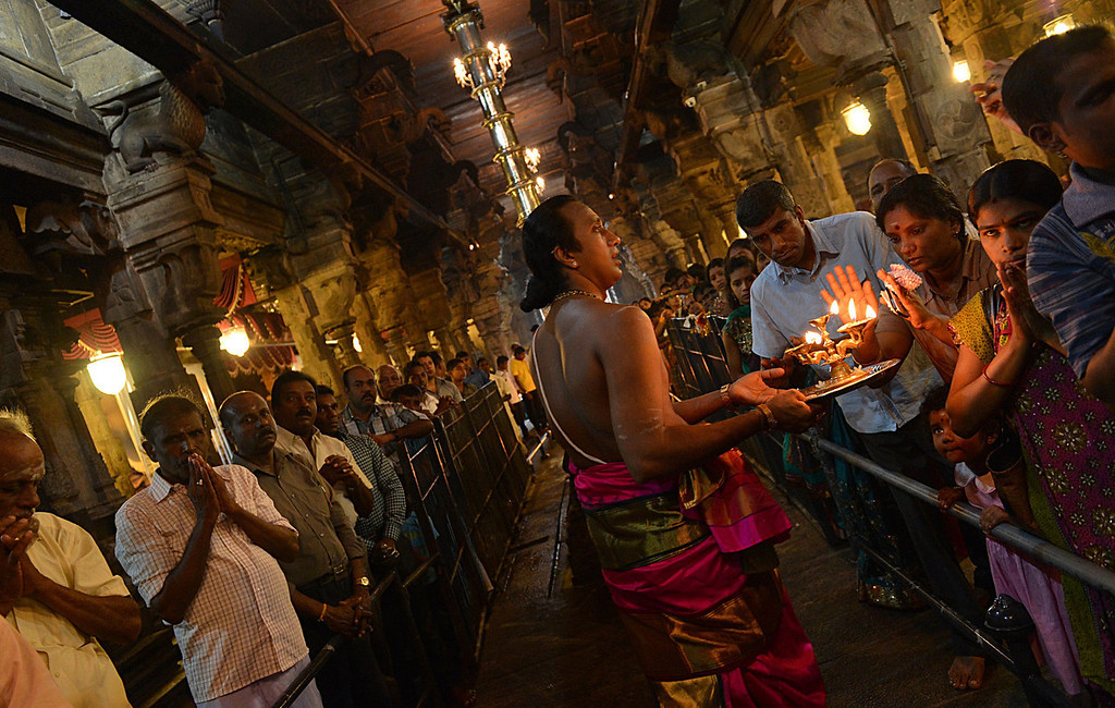 . A Sri Lankan Hindu priest blesses devotees during Diwali, or the Festival of Lights at a Hindu temple in Colombo on November 2, 2013. The Hindu Festival of Lights, Diwali marks the homecoming of the God Lord Ram after vanquishing the demon king Ravana and symbolises taking people from darkness to light in the victory of good over evil.  Ishara S.KODIKARA/AFP/Getty Images