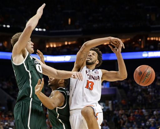 . Michigan State\'s Matt Costello, left, knocks the ball from Virginia\'s Anthony Gill, right, during the second half of an NCAA tournament college basketball game in the Round of 32 in Charlotte, N.C., Sunday, March 22, 2015. (AP Photo/Gerald Herbert)