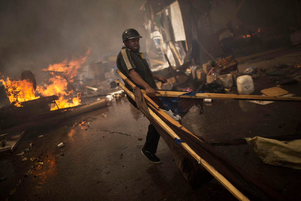 . A supporter of ousted Egyptian President Mohammed Morsi carries wood to burn in a fire barricade at the sit-in at Rabaa Al-Adawiya Square in Cairo\'s Nasr City district, Egypt, Wednesday, Aug. 14, 2013.  (AP Photo/Manu Brabo)