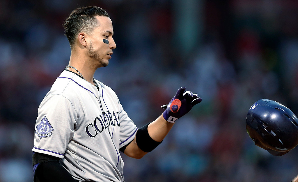 . Colorado Rockies\' Carlos Gonzalez tosses his helmet after flying out to end the third inning of a baseball game against the Boston Red Sox at Fenway Park in Boston on Tuesday, June 25, 2013. (AP Photo/Winslow Townson)