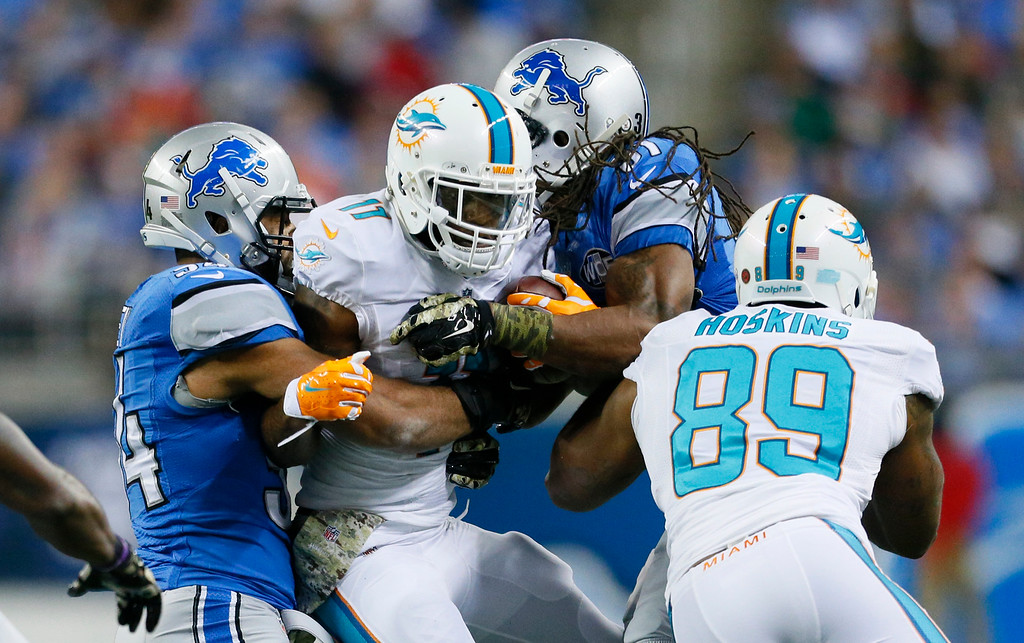 . Miami Dolphins wide receiver Mike Wallace (11) is stopped by Detroit Lions outside linebacker DeAndre Levy, left, and cornerback Rashean Mathis (31) during the first half of an NFL football game in Detroit, Sunday, Nov. 9, 2014. (AP Photo/Rick Osentoski)